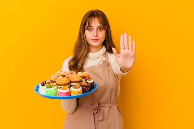 Young pastry chef woman isolated on yellow wall standing with outstretched hand showing stop sign, preventing you.
