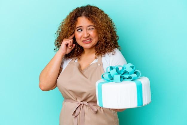 手で耳を覆う青い背景に分離されたケーキを保持している若いペストリー ラテン女性。