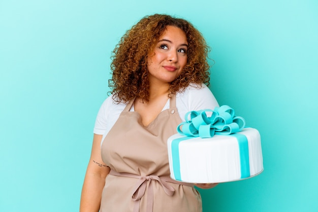 목표와 목적을 달성하는 꿈을 꾸고 파란색 배경에 고립 된 케이크를 들고 젊은 과자 라틴 여자