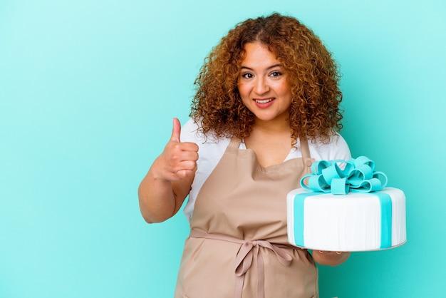 笑顔で親指を上げる青い背景に分離されたケーキを保持している若いペストリー ラテン女性