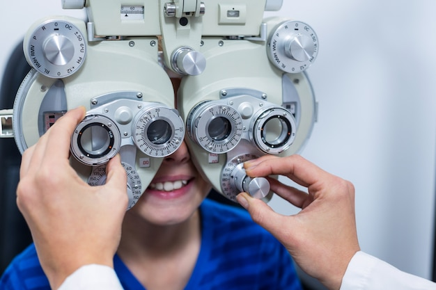 Young patient under going eye test through phoropter