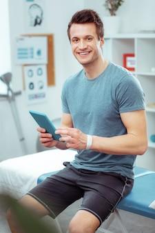 젊은 환자. 그의 의사를 기다리는 동안 의료 침대에 앉아 즐거운 젊은 남자