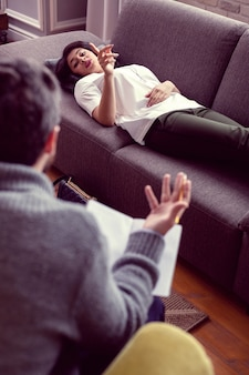 若い患者。彼女の医者に話している間彼女の指を持ち上げて素敵な美しい女性