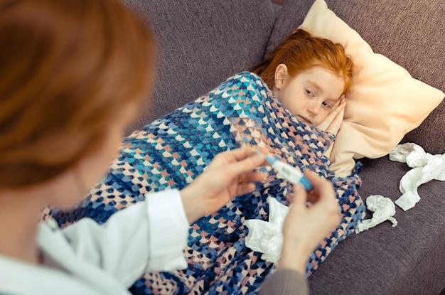 若い患者。毛布で覆われている間彼女の医者を見ている素敵な元気のない女の子