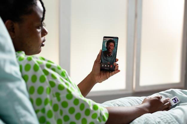 Молодой пациент африканской национальности разговаривает по видеоконференции со смартфоном, сидя на койке в больничной палате. черная девушка, использующая онлайн-интернет для связи с мужчиной