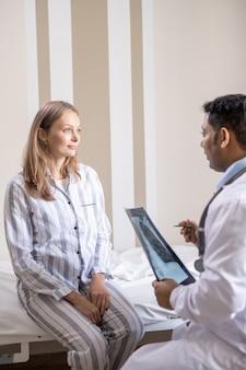 엑스레이 결과, 의료 처방 및 권장 사항에 대해 논의하는 동안 의사 앞에 침대에 앉아 있는 코비드 병원의 젊은 환자