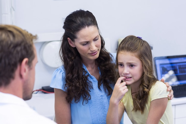 Young patient showing teeth to dentist