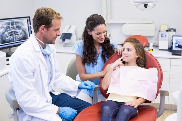 Молодой пациент показывает зубы стоматологу