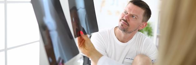 아픈 다리를 가진 젊은 환자는 병원에서 의사와 무릎 관절의 x- 선을 찾고 있습니다