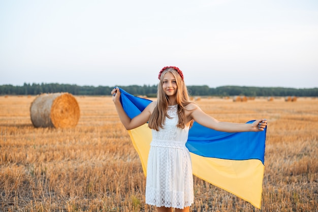 Молодая патриотичная женщина с флагом украины на убранном поле пшеницы с тюками соломы