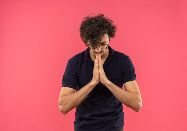 Young peaceful man in black shirt with optical glasses holds hands together pretending to meditate isolated on pink wall