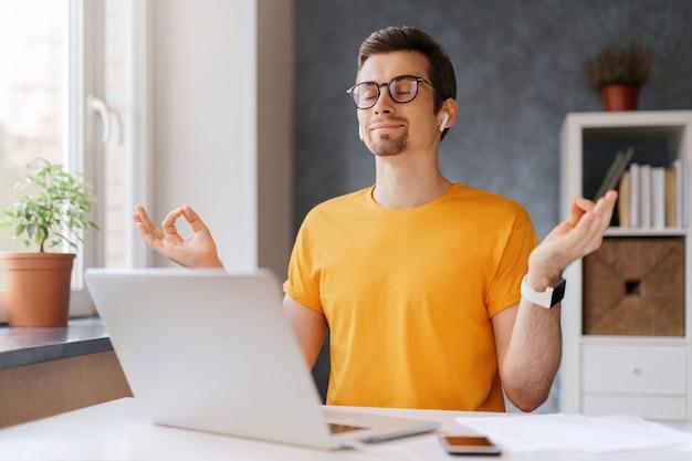 젊은 평화로운 마음을 가진 남자는 노트북으로 집에서 원격으로 일하면서 침착하고, 웃고, 편안하고, 명상을 유지합니다.
