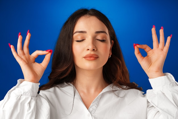 Young peaceful woman keeping eyes closed while meditating against blue background