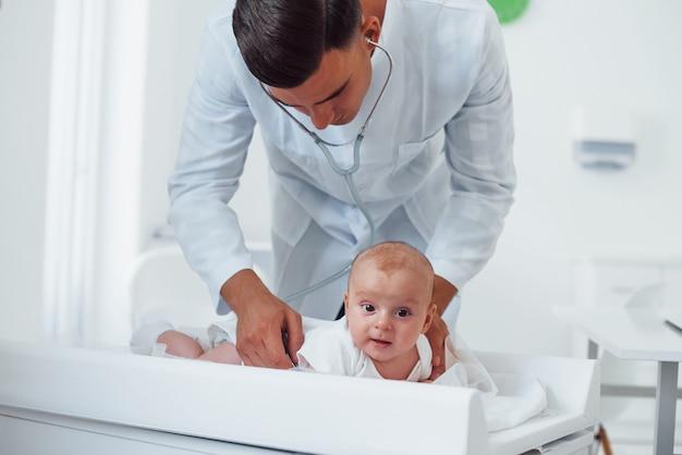 젊은 소아과 의사는 낮에 병원에 작은 아기와 함께 있습니다.