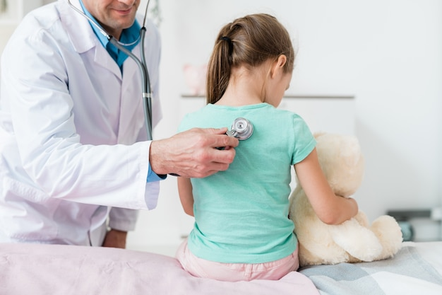 Young pediatrician in whitecoat examining back of little girl with stethoscope in medical office