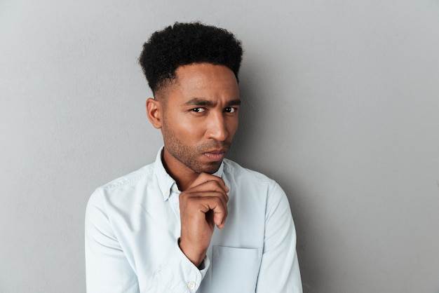 Young pensive african man looking closely at camera