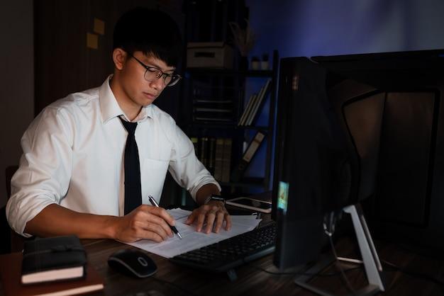 遅く集中して深刻に働く若い物思いにふけるアジア人