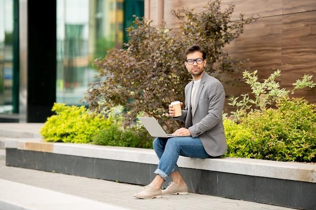 Молодой задумчивый автор в элегантной повседневной одежде с напитком, обдумывая новые идеи для новой книги в городской среде
