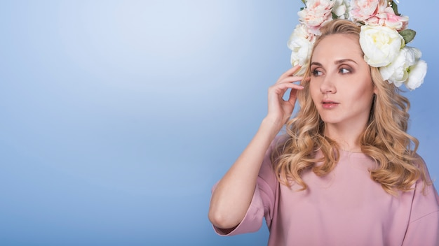 Young pensive blond lady with beautiful flower wreath