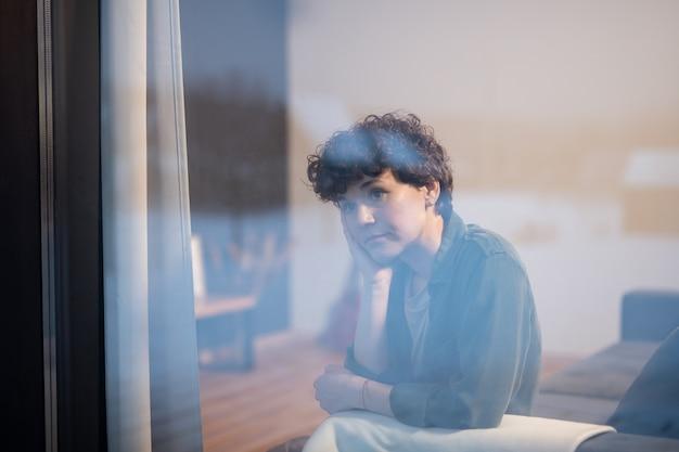 夜のリビングルームの窓際のソファに座って、夜の街の景色を見ているカジュアルウェアの若い物思いにふけるブルネットの女性