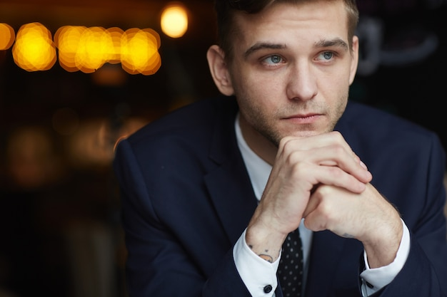 Young pensive businessman in cafe