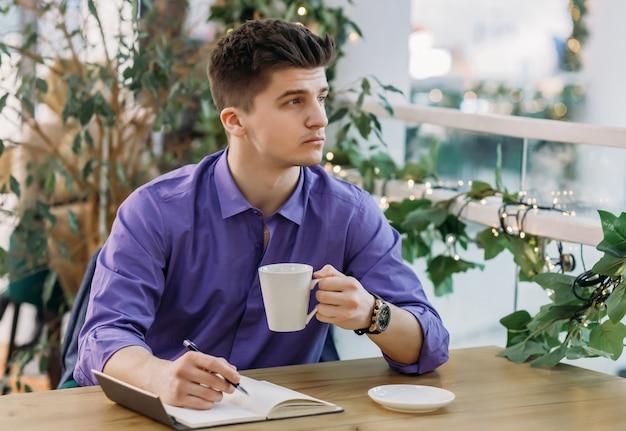 袖をまくり上げたシャツを着た若い物思いにふけるビジネスマンは、ビジネスを考えている間、彼の手でコーヒーを持って、横を向いています