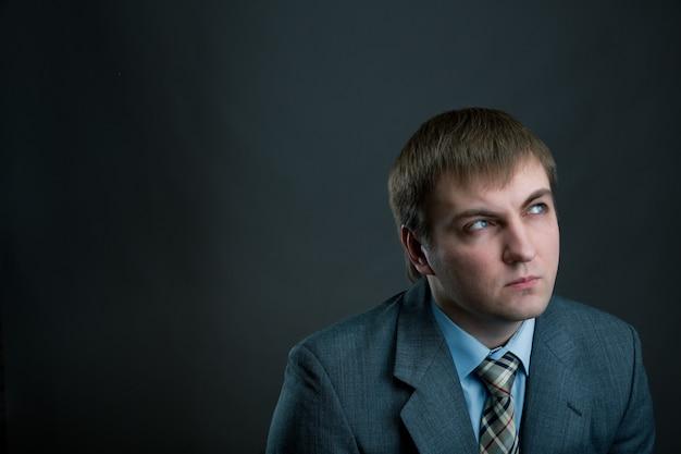Молодой задумчивый бизнесмен в костюме и галстуке на черном