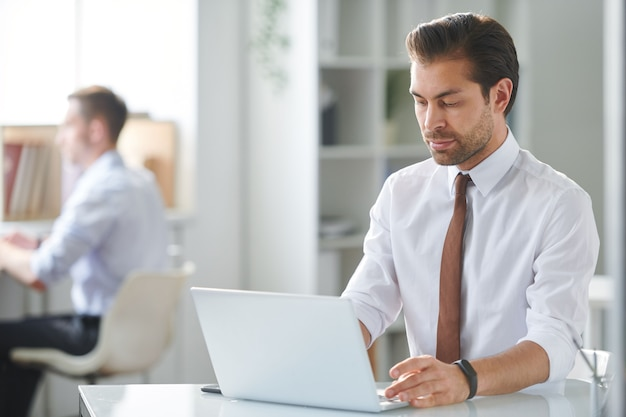 Young pensive businessman reading online information on laptop display while sitting by desk