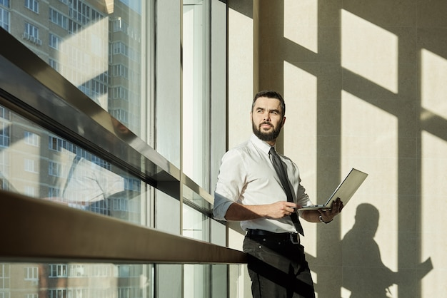 노트북이 프레젠테이션을 준비하거나 사무실 센터의 창으로 새로운 비즈니스 프로젝트를 통해 작업하는 젊은 잠겨있는 사업가