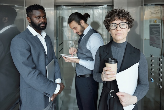 Young pensive businesswoman with glass of coffee and paper moving in elevator with two intercultural men