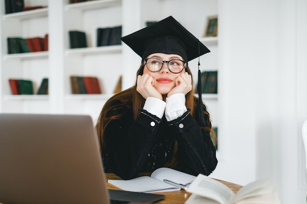 Молодая задумчивая студентка колледжа кавказской в выпускном костюме, сидя перед ноутбуком