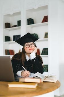 Молодая задумчивая студентка колледжа кавказской в выпускной форме