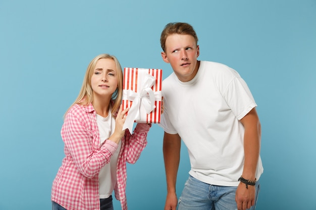 Young pensive couple two friends guy and woman in white pink t-shirts posing