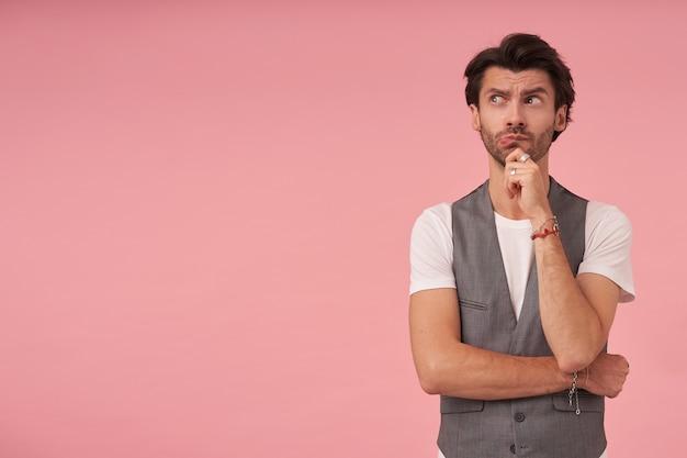 Giovane uomo dai capelli scuri pensieroso in gilet grigio e maglietta bianca in piedi su sfondo rosa, guardando da parte con viso pensieroso e tenendo il mento con la mano, fronte accigliata e contratta