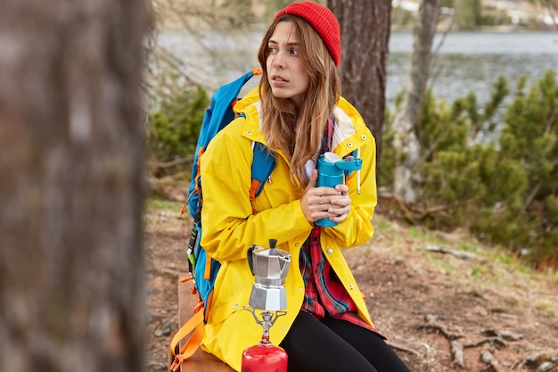 Молодая задумчивая самочка с рюкзаком сидит в небольшом лесу у речки или озера, греется горячим напитком из термоса, варит кофе на походной плите