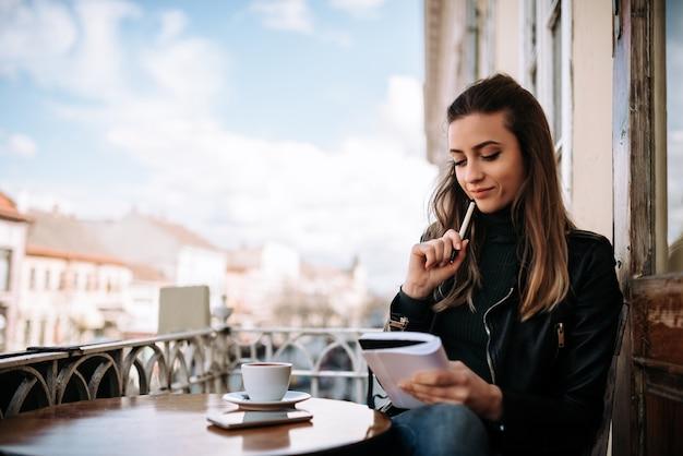 テラスに座っている若い物思いにふける女性作家。