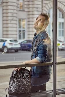 Молодой задумчивый человек стоит на остановке общественного транспорта с рюкзаком.