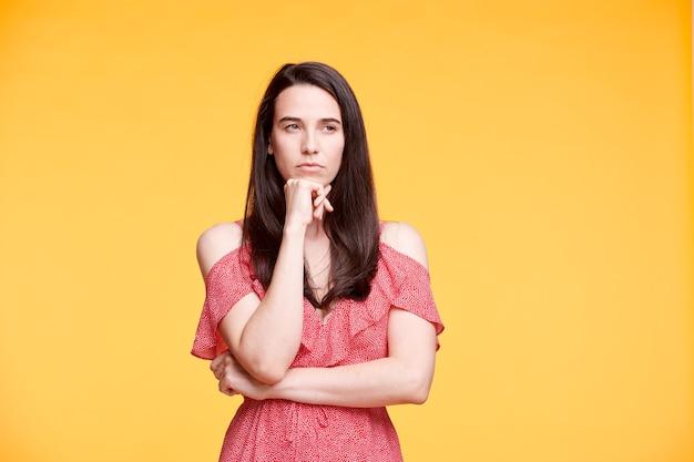 黄色の壁を越えてポーズをしながらあごで片手を保つ赤いエレガントなドレスの若い物思いにふけるまたは不満の女性