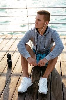 Young pensive sportsman listening to music in earphones, looking away, sitting on pier