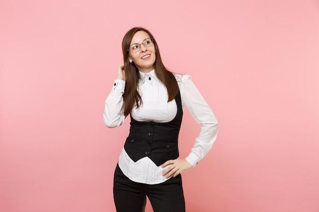 Молодая задумчивая успешная бизнес-леди в очках, держа руку возле головы, глядя в сторону, изолированную на пастельно-розовом фоне. леди босс. концепция богатства карьеры достижения. скопируйте место для рекламы.