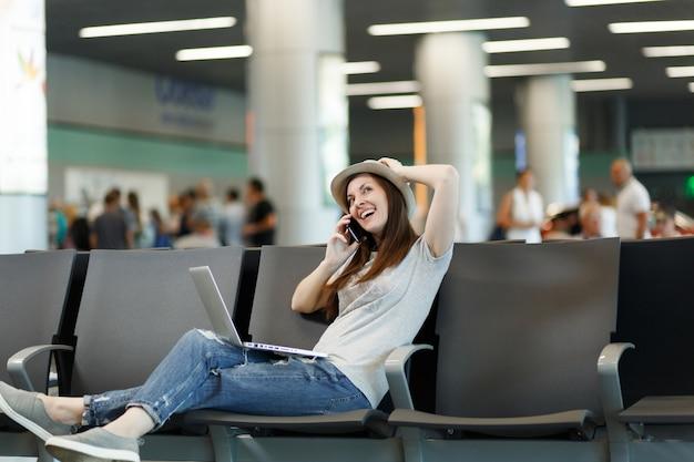 Giovane donna turistica viaggiatrice pensierosa che lavora al laptop, parla al telefono cellulare, chiama un amico all'aeroporto