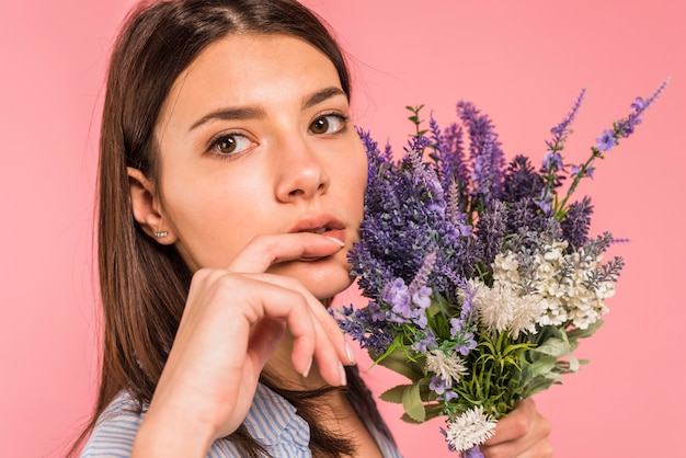 Young pensive woman holding bunch of flowers near face
