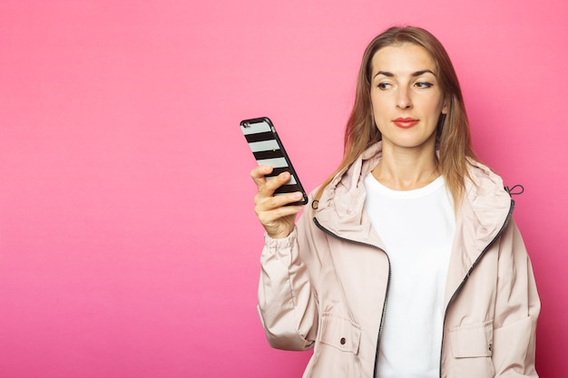 Young pensive woman holding phone, pink isolated.