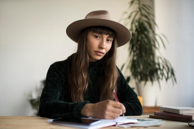 Молодая задумчивая женщина в стильной шляпе, сидя на рабочем месте