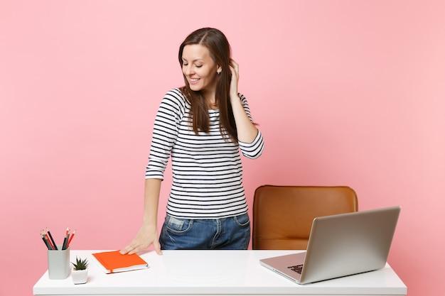 仕事を見下ろし、現代的なpcのラップトップで白い机の近くに立っている若い物思いにふける女性