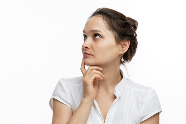 Young pensive woman. pretty brunette. close-up. white background.