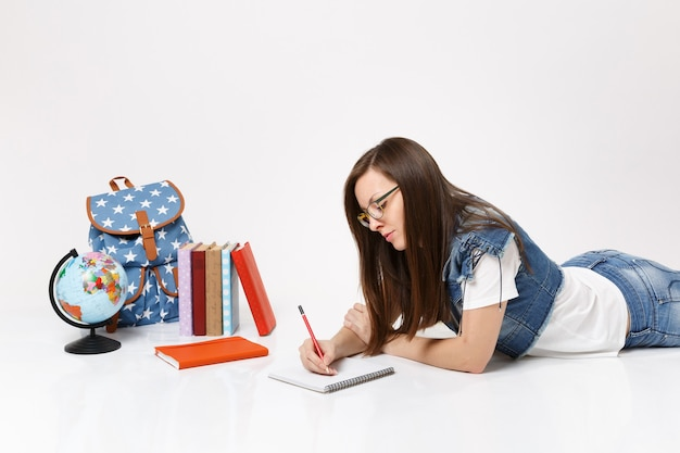 Young pensive woman student in denim clothes, glasses writing notes on notebook and lying near globe, backpack, school books isolated