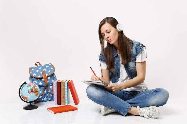 Young pensive woman student in headphones listening music writing notes on notebook sitting near globe backpack, school books isolated