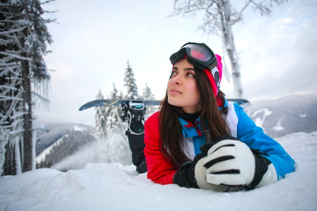 Young pensive woman in winter in snowy forest on top of mountains
