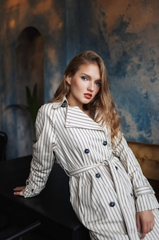 Young pensive woman with wavy hair in striped trench coat leaning on table dreamily